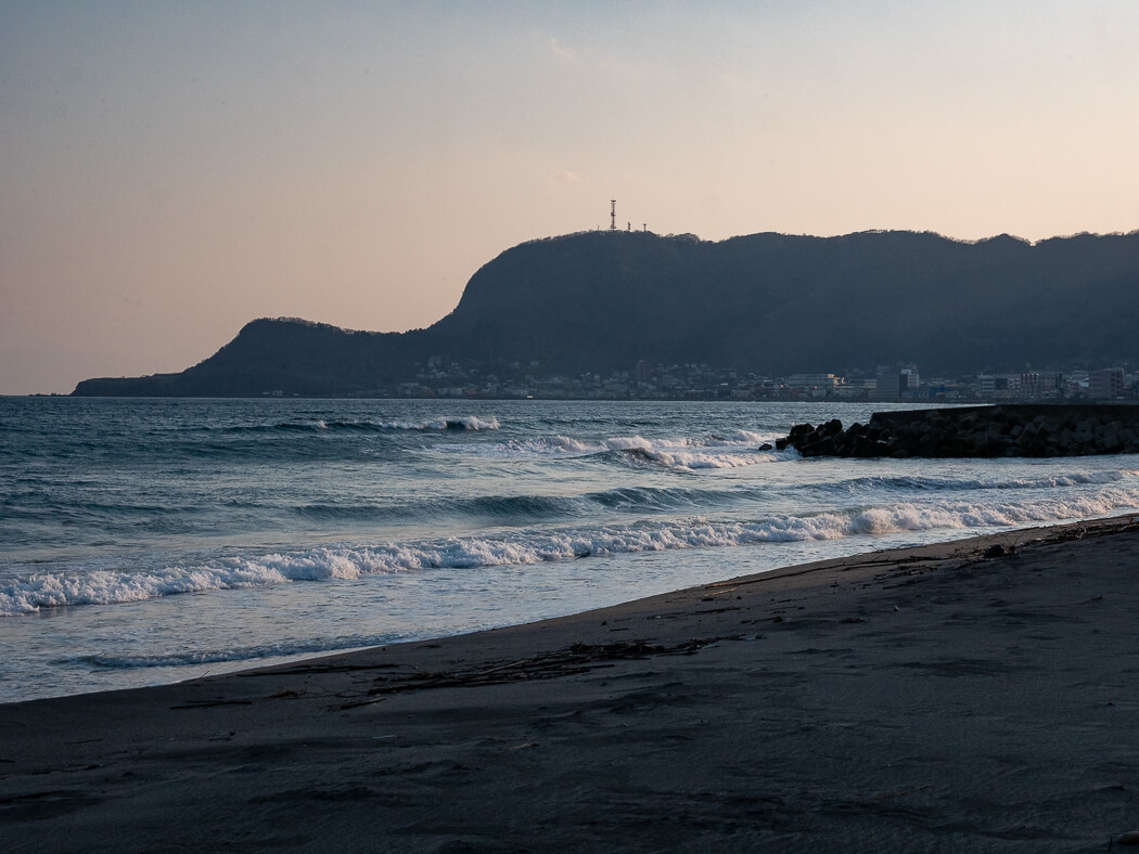 Waves lap up onto Hakodate Beach with Mt Hakodate in the background