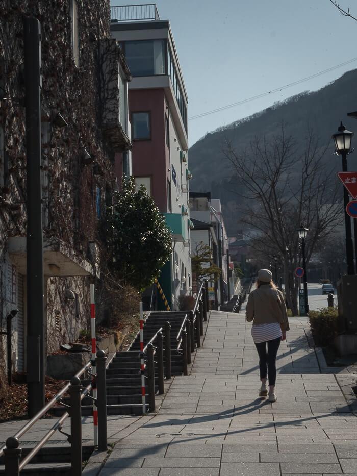 A girl walks up pretty Hachiman Zaka street