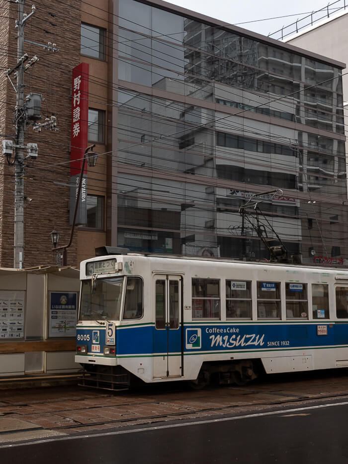 A tram pulls up to the stop in front of a building