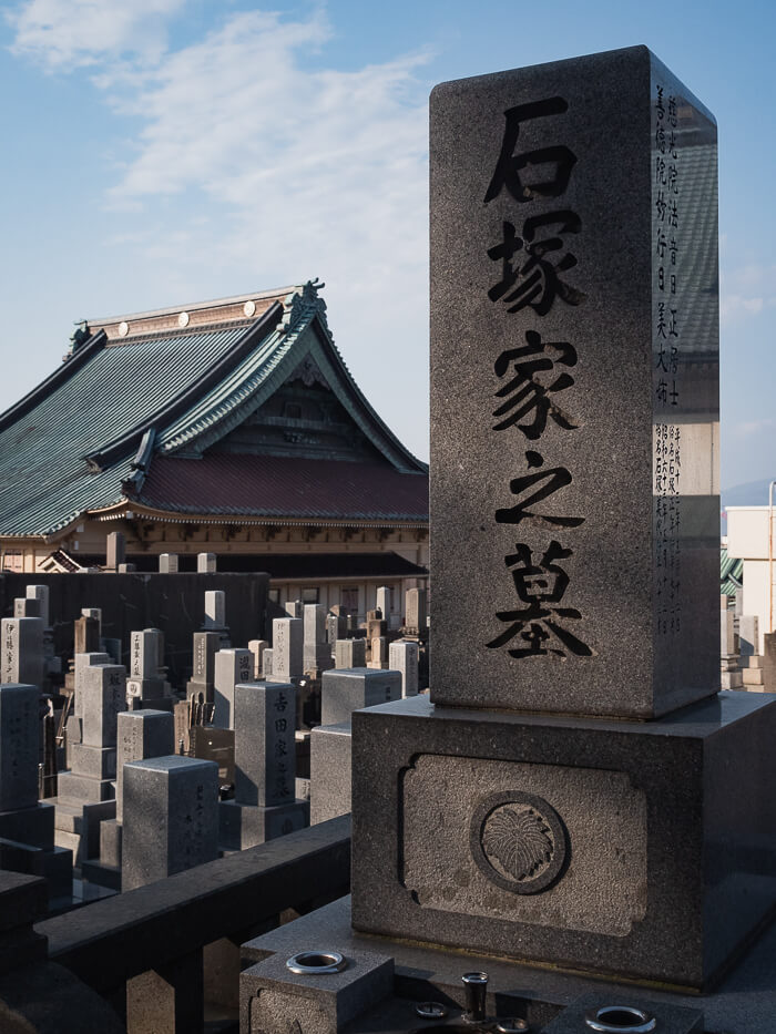 A tombstone with a temple in the background