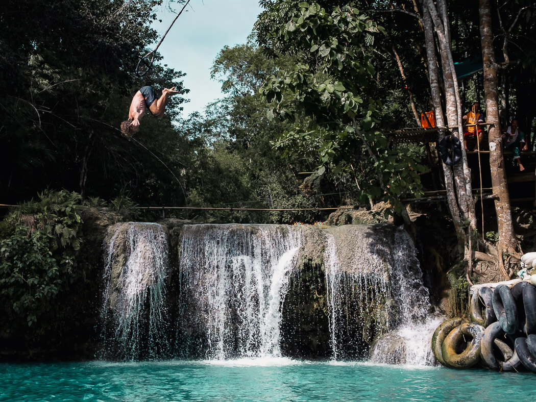 A man somersaults through the air at Cambugahay Falls