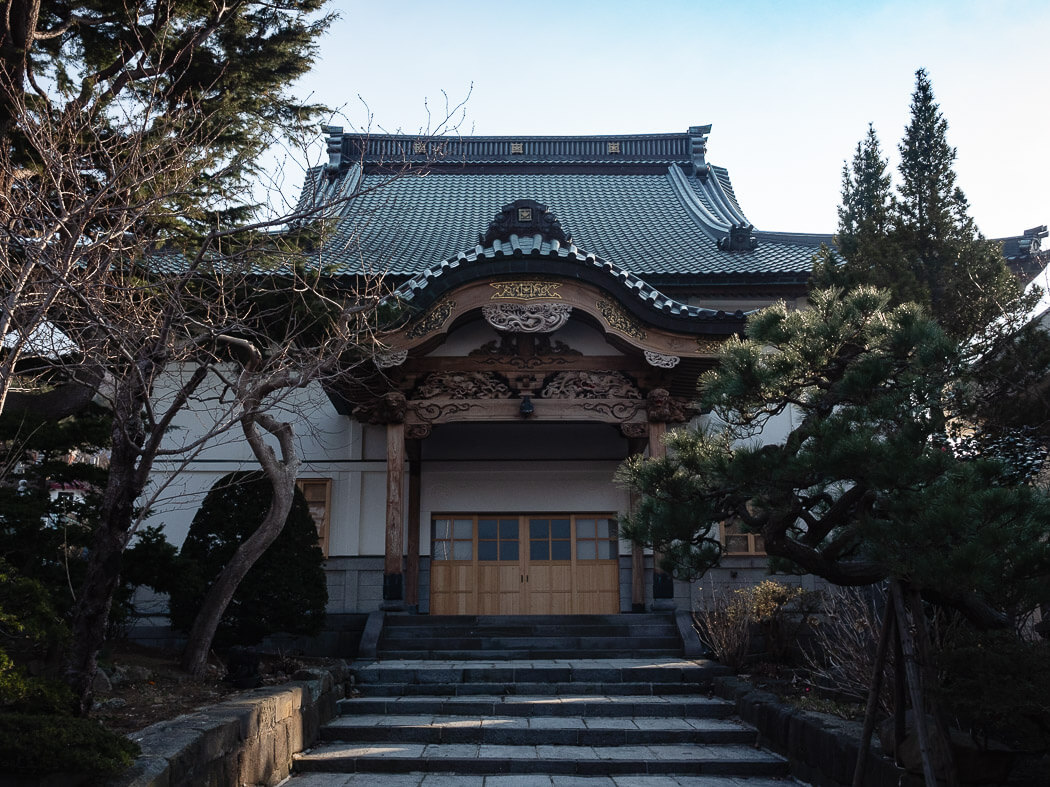 Jitsugyo-Ji temple with trees surrounding the walkway up to it