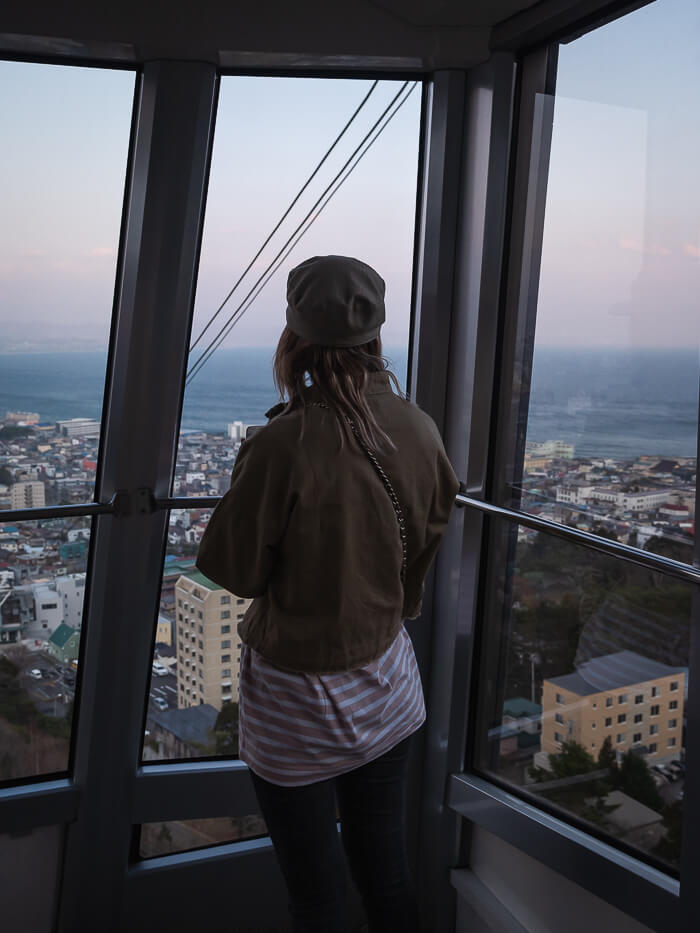 A girl looks out of the window of the Mt Hakodate ropeway carriage