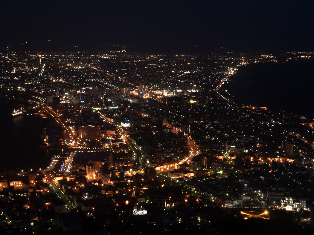 A view of Hakodate city during the night, with lights illuminated against the night sky
