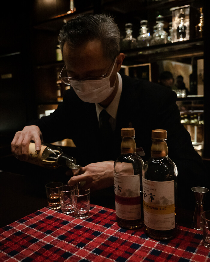 A man pours whisky behind the bar at Yoichi Nikka Whisky Distillery