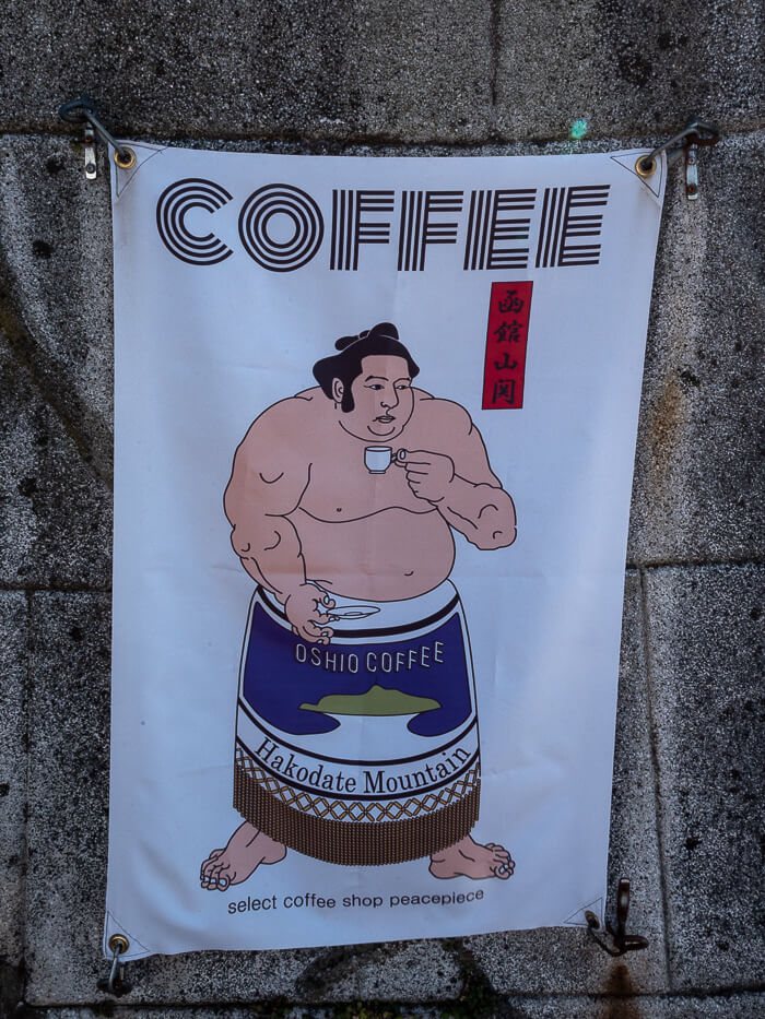 A poster of a sumo wrestler advertising coffee from Peace Piece