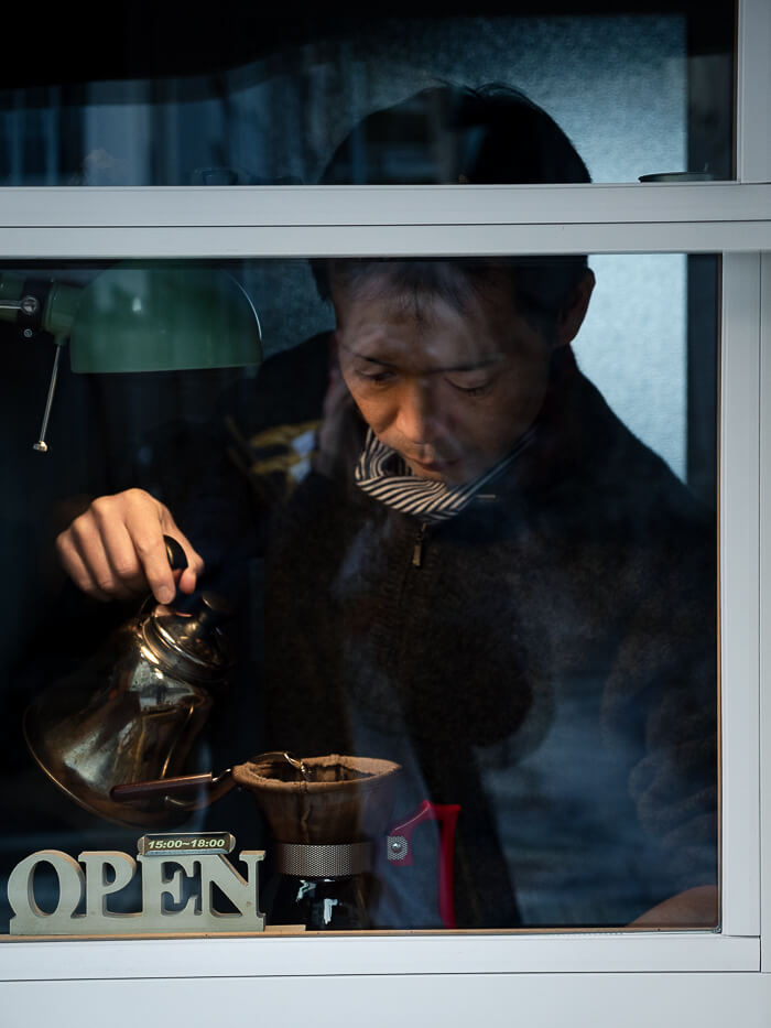 A man drip pouring coffee behind a window