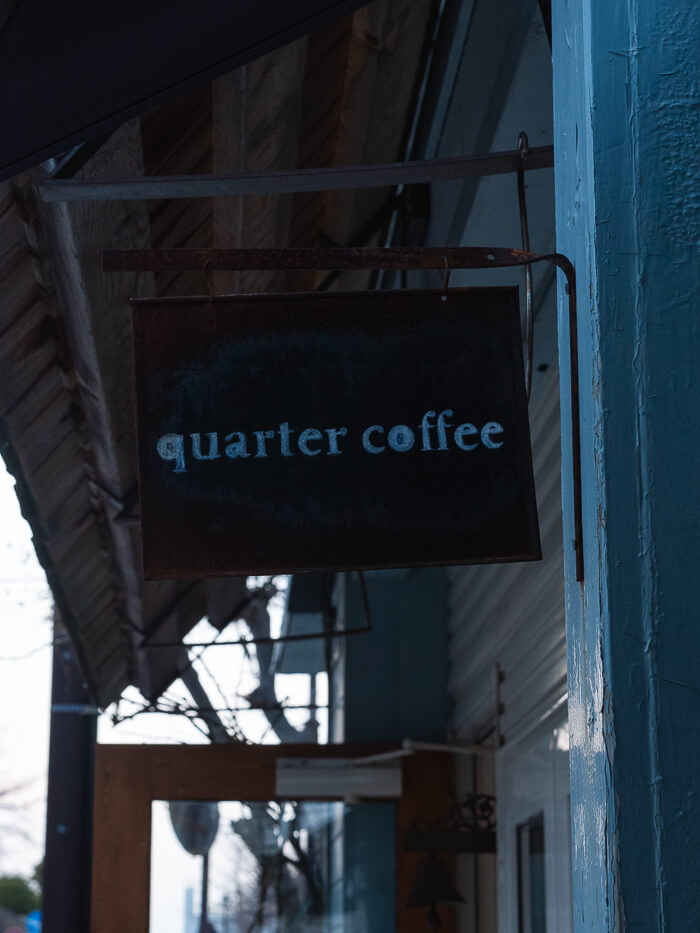 A sign hanging from a shop door reading 'quarter coffee'