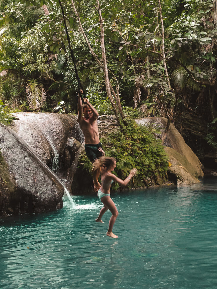 A couple rope swing into blue water, one of them let go too early