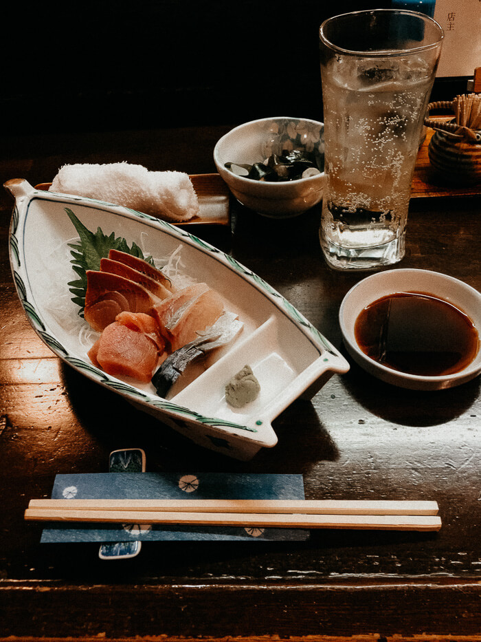 Sashimi on a boat plate with a highball and soy sauce