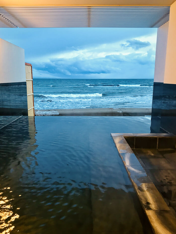An open-air onsen bath leads out to sea