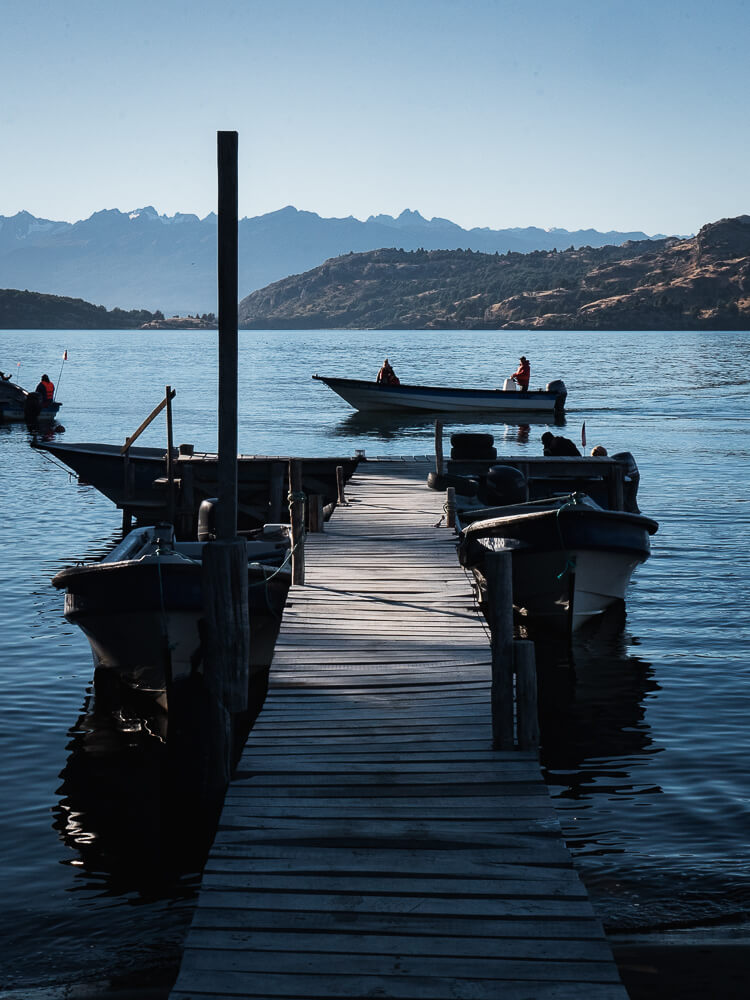 Speedboat sailing past wooden dock with mountains in background
