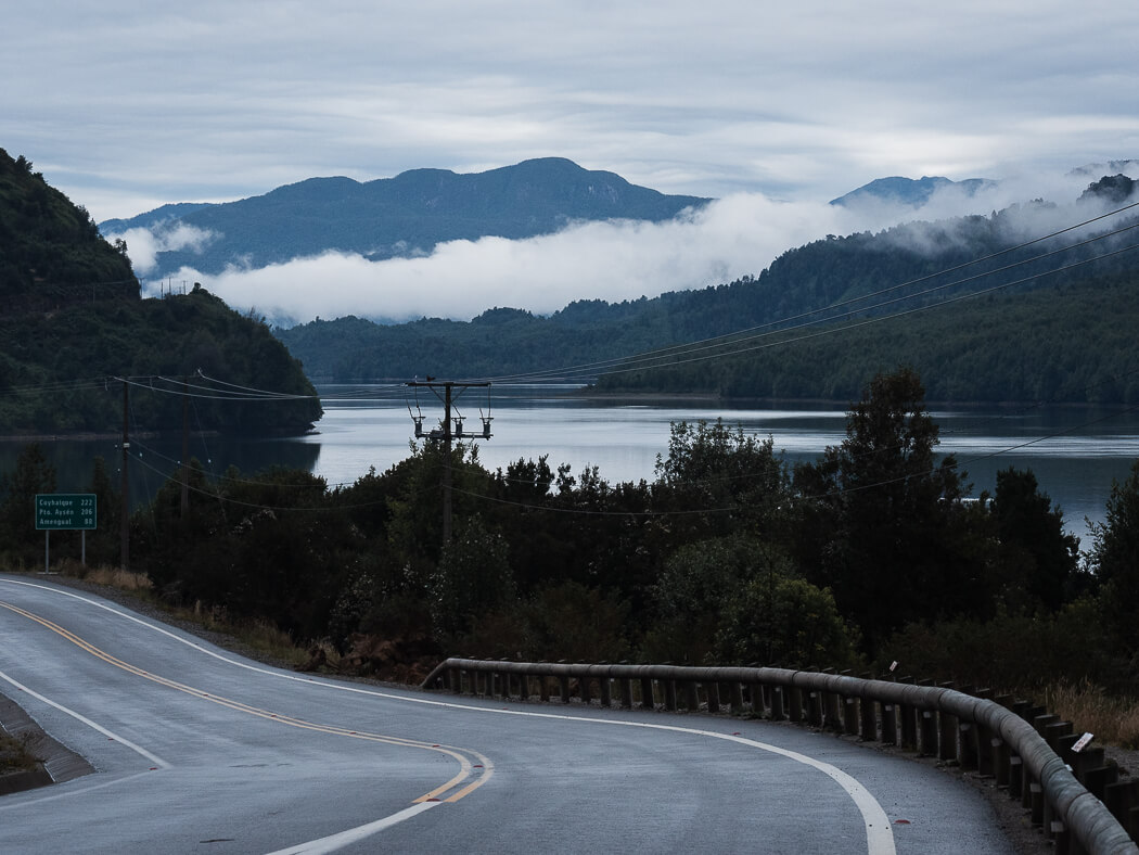 A road winds around the seaside with clouds hanging low over green hills