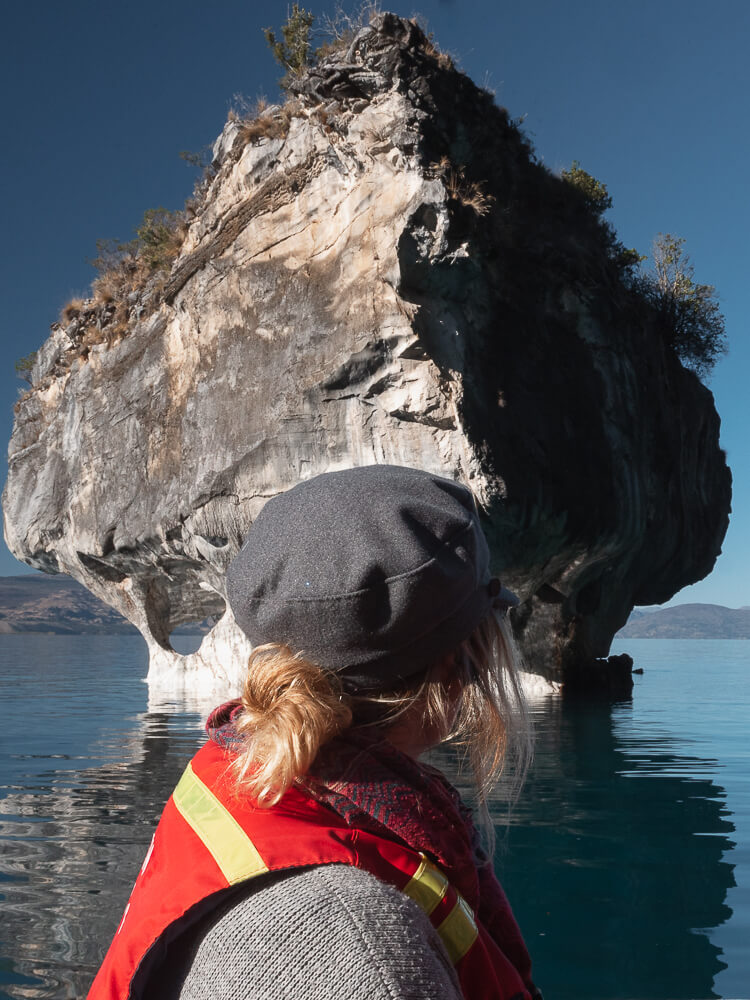 Girl with lifejacket looking at large rock formation from boat