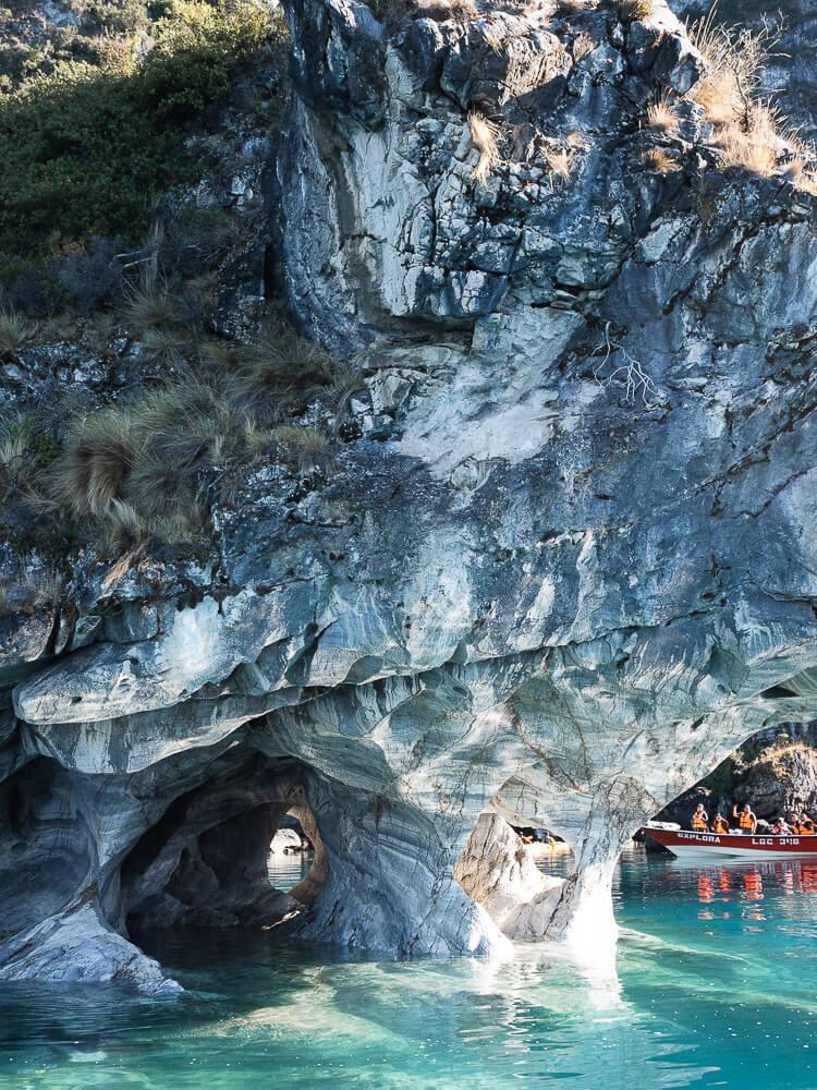 Speedboat on lake next to large rock formation