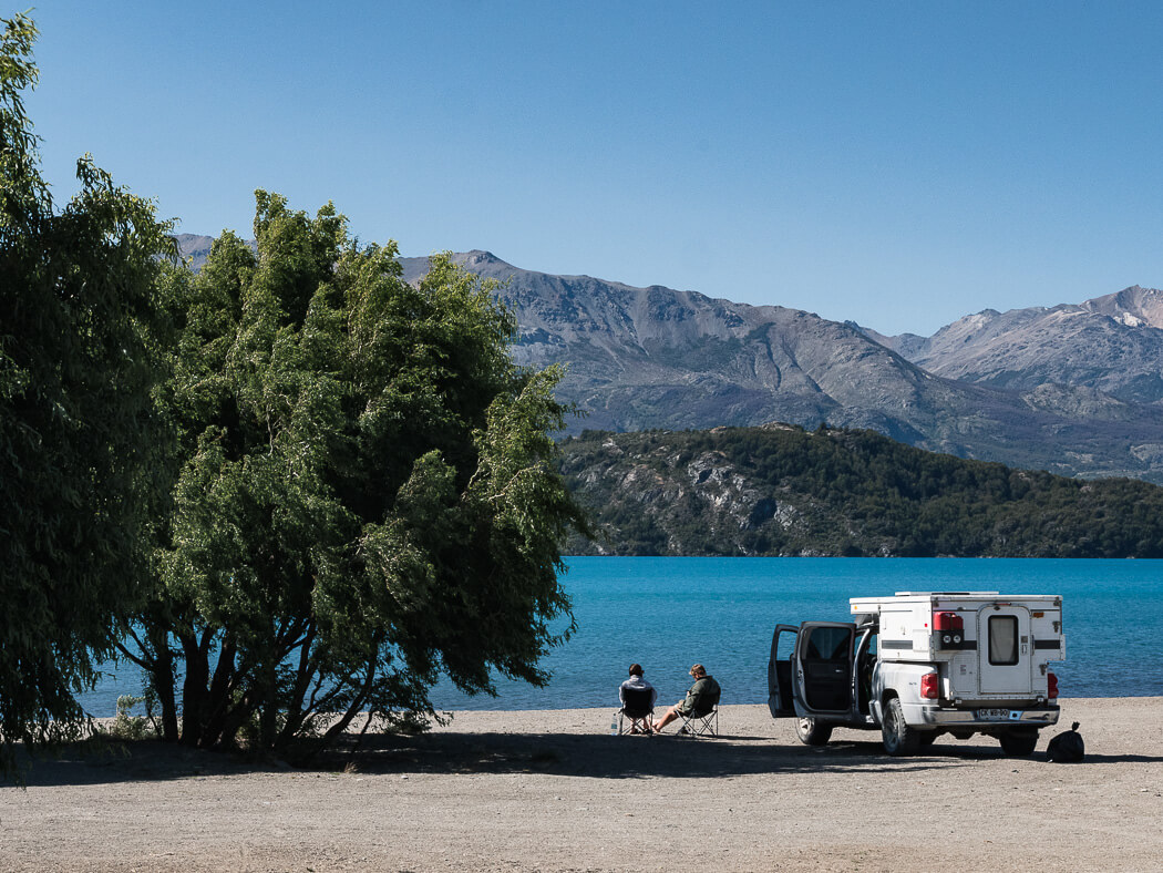 Couple sitting in front of campervan on beach