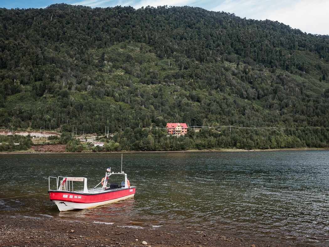 A red and white boat is moored in the water in Puyuhuapi with green hills surrounding