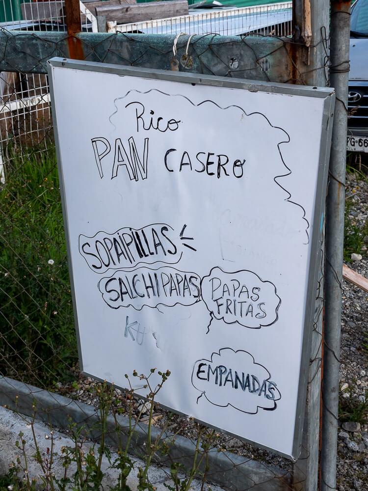A whiteboard which reads 'pan casero, sopapillas, salchipapas'