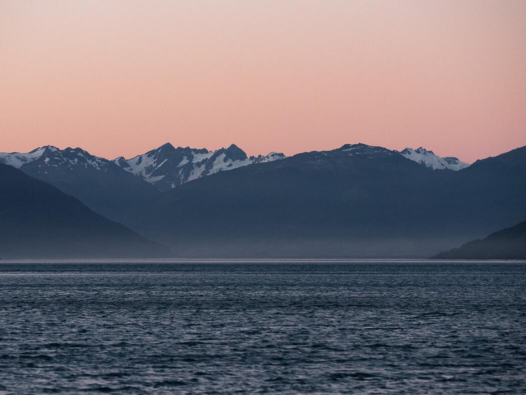 Sun set over snowy mountain range from beach at Puerto Rio Tranquilo