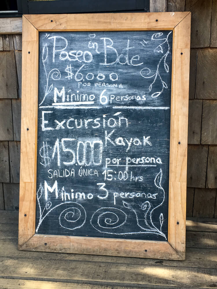 A chalkboard showing prices for a kayak tour