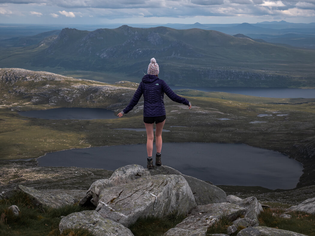 girl standing at mountain summit of Ben Hope in Scotland